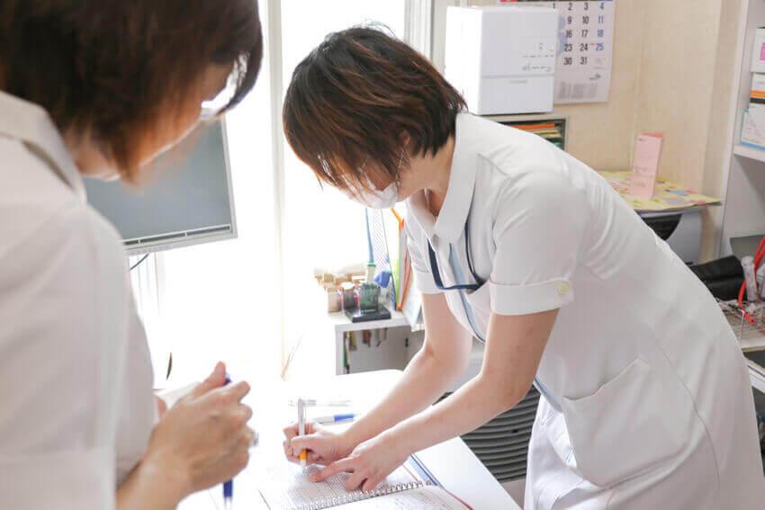 書き物をしている看護師